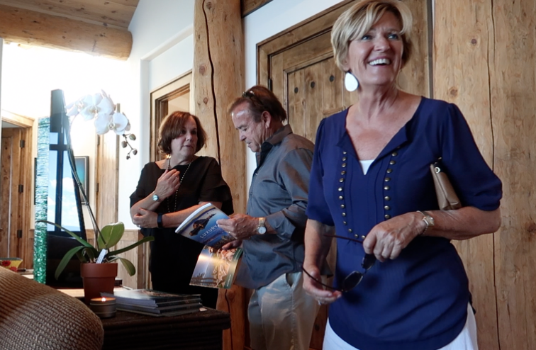 Sue Lowe with guests welcoming them to South Peak Lodge, a stunning home with outstanding views of Lake Tahoe.